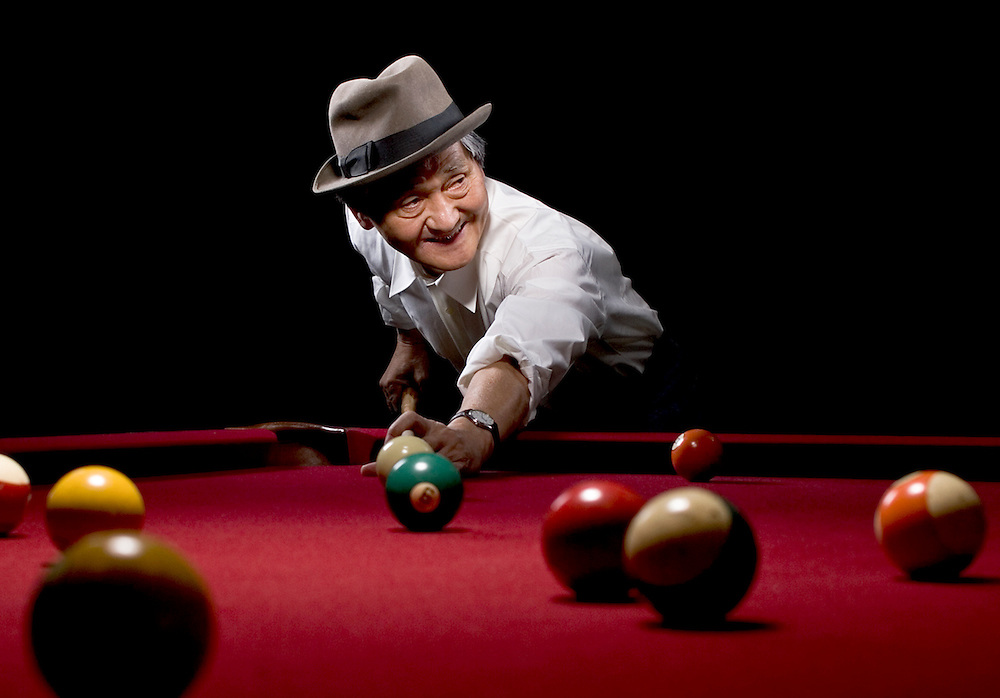 image of an older asian man playing a game of billiards