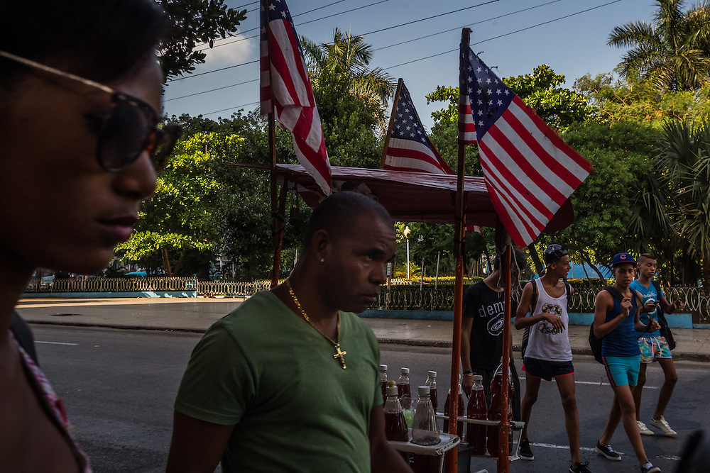 HAVANA, CUBA - JULY 20, 2015: Cubans walk past a snowcone cart decorated with American flags in Havana. After more than half a century defined by mistrust and rancor, the United States officially reopened its six-story embassy in Havana today, marking a watershed moment of transition for the two countries as they lean toward closer diplomatic ties and ease past one of the last remnants of the Cold War.  President Barack Obama, when announcing an end to the diplomatic freeze, eased travel restrictions, opened the door for more remittances to Cuba and expanded the amount of goods that visiting Americans could bring back home – like Cuban cigars and rum. He even removed the country from the list of nations that sponsor terrorism. President Raul Castro, meanwhile, has spent the last five years, before the thaw even began with the Obama administration, attempting to alter his nation's economic dysfunction, ordering the firing of government employees, encouraging a slow but fresh influx of Cubans into self-employment and even creating a special economic zone in the coastal city of Mariel to attract foreign investment.  PHOTO: Meridith Kohut for The New York Times