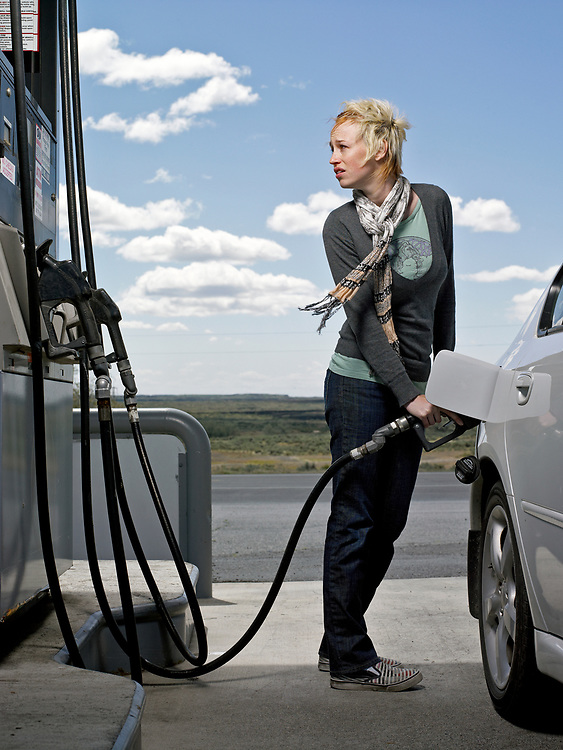 30's something woman pumping gas at gas station.