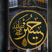 Tourists look from the balcony of the second floor of Hagia Sophia with one of the massive medallions with calligraphy in the background.  The medallions have the names of Allah, the Prophet Muhammad, the first four caliphs Abu Bakr, Umar, Uthman and Ali, and the two grandchildren of Mohammed: Hassan and Hussain, by the calligrapher Kazasker İzzed Effendi (1801–1877). Originally built as a Christian cathedral, then converted to a Muslim mosque in the 15th century, and now a museum (since 1935), the Hagia Sophia is one of the oldest and grandest buildings in Istanbul. For a thousand years, it was the largest cathedral in the world and is regarded as the crowning achievement of Byzantine architecture.