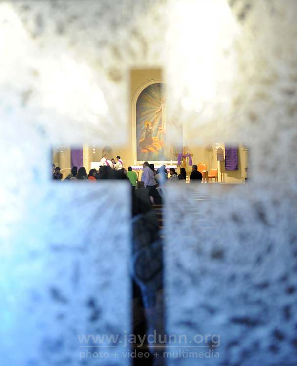 Seen through the frosted glass of the entryway, churchgoers at Sacred Heart in Salinas line up to receive blessings on Ash Wednesday.