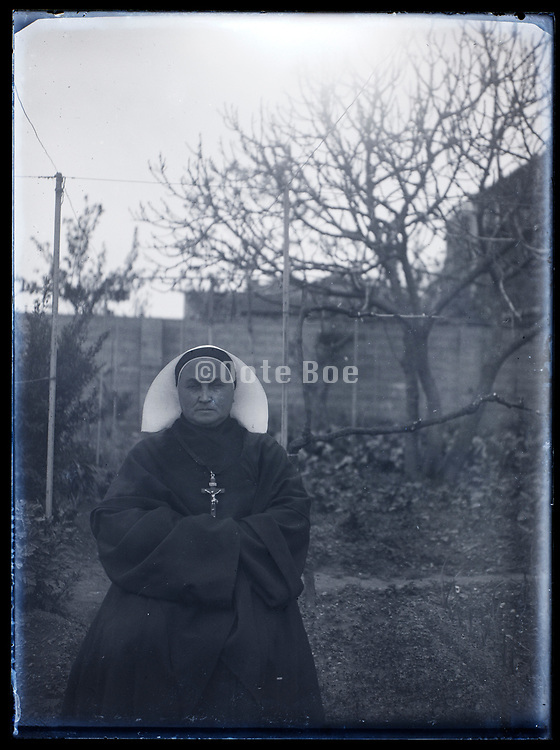 portrait of a nun sitting in a backyard France 1933