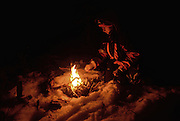 Young woman prepares bonfire in the snow, at night. Inari, Lapland