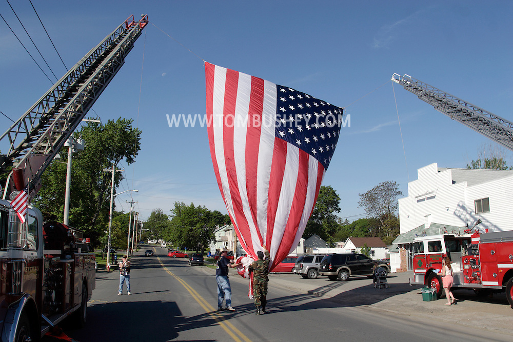 Middletown, NY - A veteran, center, holds a large American flag as it is is raised between the ladders of two fire engines before the start of the Middletown-Wallkill Veterans Council Memorial Day ceremonies and parade on May 26, 2008.