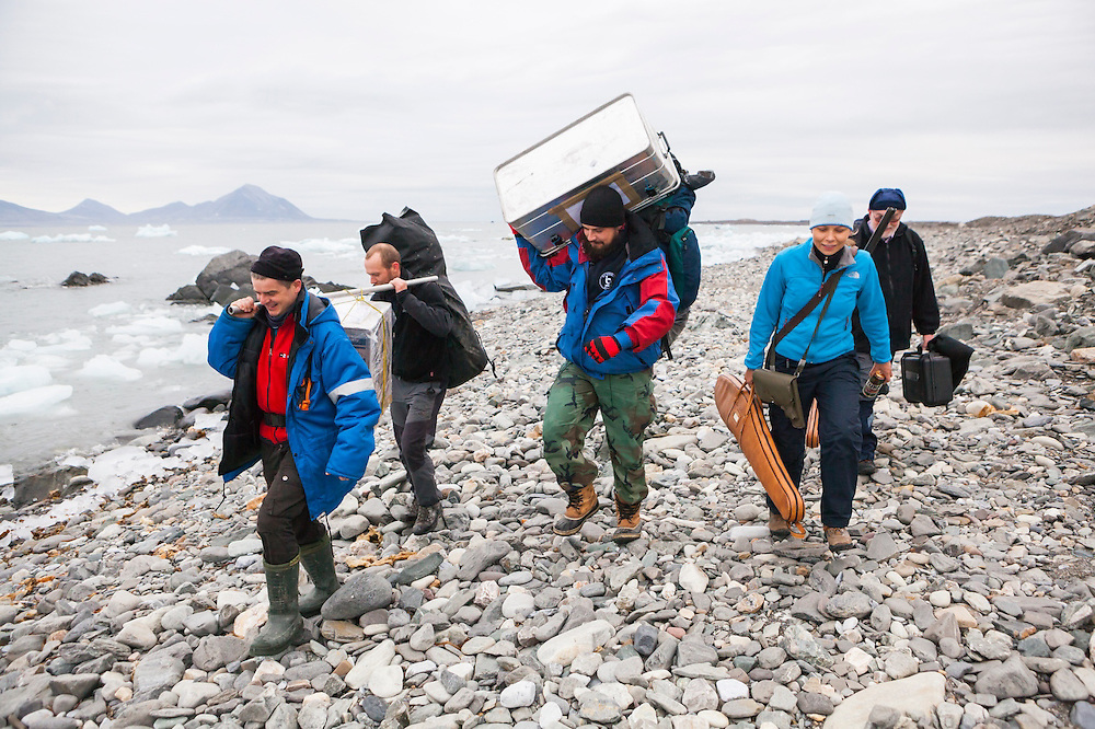 Polish scientists departing the Polish Polar Station in Hornsund, Svalbard hike to a beach where they can be picked up by boat.