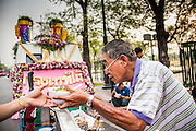 12 APRIL 2013 - BANGKOK, THAILAND:  A noodle vendor serves breakfast to people waiting for the start of the annual Songkran procession in Bangkok. The Phra Buddha Sihing, a revered statue of the Buddha, is carried by truck through the streets of Bangkok so people can make offerings and bathe it in scented oils. Songkran is celebrated in Thailand as the traditional New Year's Day from 13 to 16 April. The date of the festival was originally set by astrological calculation, but it is now fixed. If the days fall on a weekend, the missed days are taken on the weekdays immediately following. Songkran is in the hottest time of the year in Thailand, at the end of the dry season and provides an excuse for people to cool off in friendly water fights that take place throughout the country. The traditional Thai New Year has been a national holiday since 1940, when Thailand moved the first day of the year to January 1. The first day of the holiday period is generally the most devout and many people go to temples to make merit and offer prayers for the new year. .  PHOTO BY JACK KURTZ