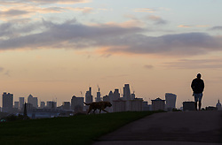 London, September 11 2017. A dog walker in silhouette against the London skyline as a new day breaks over the city. © Paul Davey