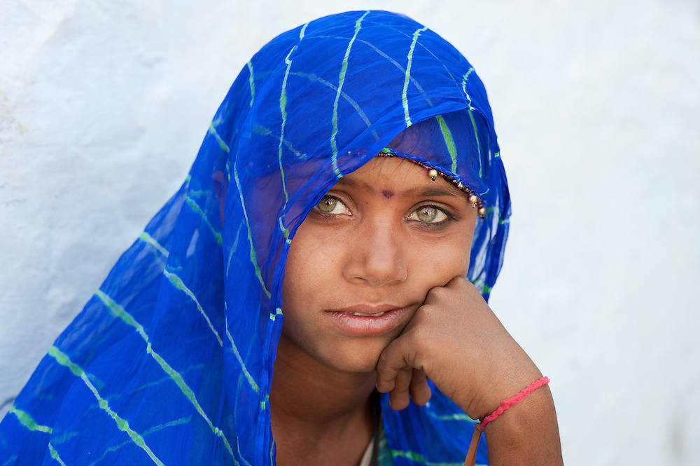 Portrait of a stunningly beautiful young girl from Rajasthan with light coloured eyes and dressed in blue colour. Thar desert, India.