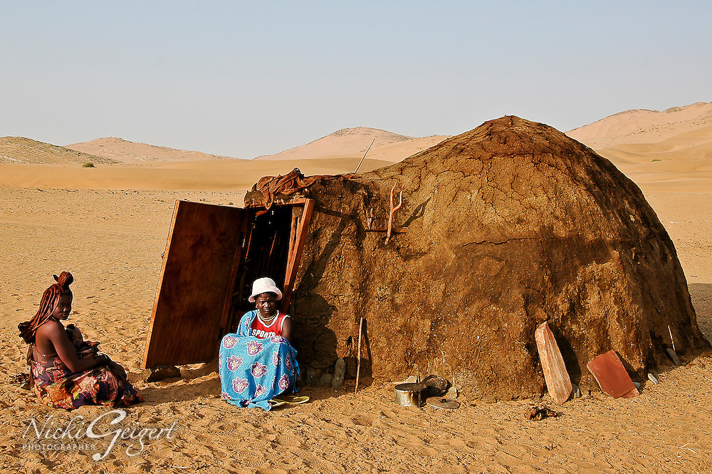 Himba woman with child and old woman sitting by a mud hut in Namibia, Africa. Fine art photography print.<br /> <br /> DSC2512