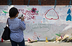 © Licensed to London News Pictures. 20/06/2017. London, UK. A woman takes a photograph of messages written on a banner placed on a wall outside Finsbury Mosque in north London after a van ploughed into a crowd nearby. One person has been killed and 10 people are injured. Darren Osborne, 47, from Cardiff, continues to be held on suspicion of attempted murder and alleged terror offences.  Photo credit: Peter Macdiarmid/LNP
