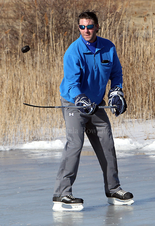 (Quincy, MA - 1/27/13) Chad Balog of Quincy plays with a puck on a frozen tidal pond in Quincy, Sunday, January 27, 2013. Staff photo by Angela Rowlings.
