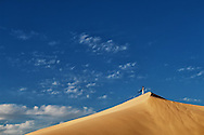 A traditional dressed moroccan man stands on a sand dune against a cloudy blue sky, Sahara desert, Morocco.