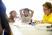 (L to R) Jacobi Jackson, 3, and Jaden Singleton, 5, wait while their mother completes paperwork at the Immunization Collaboration of Tarrant County in Fort Worth, Texas on August 30, 2013. The Immunization Collaboration offers low cost vaccines targeting hepatitis, the flu, chickenpox, measles, mumps and HPV amongst other illnesses. (Cooper Neill / for The Texas Tribune)