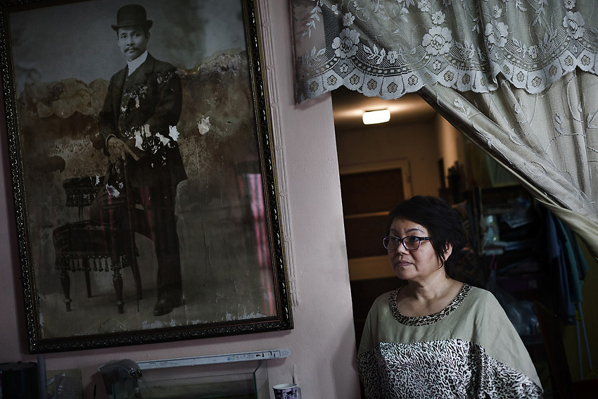 """April 2013 - Mrs Suporn Rujapan stands in her living room next to the """"King Rama V"""" portrait. The paint shows the level reached by the water during the flood in the area. She stayed in her home for the entire duration of the flood. After initially finding herself a victim of the disaster, she quickly grew into a role as front-line leader of her community's relief efforts, directing government and volunteer resources and becoming a minor media celebrity in the process.<br /> Muang Aek, north west Bangkok. © Giorgio Taraschi for The Rockefeller Foundation/Next City"""