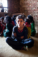 Sundar (center, in black), 8-9 years, sits amongst other rag-picker's children as they learn basic numerics in the Nai Duniya activity center in remote Lodha Basti, Manana village, Samalkha town, Haryana, India on 15th June 2012. Sundar walks 1.5km to and from her rag-picking work each day. Most of these children are rag-pickers themselves. They are now able to go to school from 8-12 in the morning, and study again at the activity center after work at 4pm. A new program to encourage the rag-picker's children to attend school is underway, to keep them from becoming the next generation of rag-pickers in cities. Photo by Suzanne Lee for The National