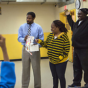 WASHINGTON, DC - APR 24:  Simon Elementary school parent Layana Campbell, picks raffle numbers with dean of students Tyrone Pittman (left), and parent volunteer Clerence Barnes, in the cafeteria at Simon Elementary School in Washington, DC, April 24, 2014. DC has enormous truancy rates, even among young children. In the last year or two, the school system has made a big push to improve attendance. Simon Elementary is seen as a model, introducing incentives and games that are tied to attendance and meant to get kids excited about coming to school; systems to ensure that parents get a call home whenever their kids are absent; weekly attendance meetings to talk about kids who are missing too much school; and a partnership with a community based organization that can make home visits and connect families with services. (Photo by Evelyn Hockstein/For The Washington Post)