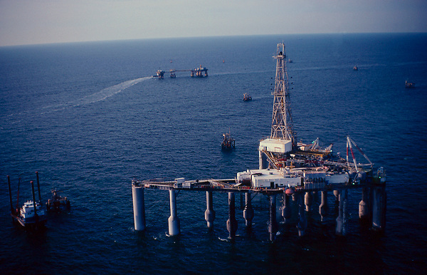 Stock photo of an offshore production platform with drill rig aboard. Lift boat to the left and production platforms nearby in the Gulf of Mexico.Stock picture,stock images,stock,photos,pictures,images