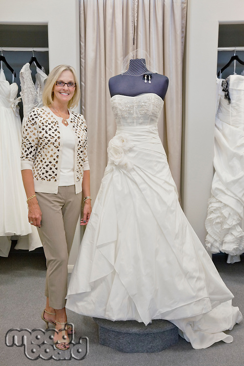 Portrait of a happy woman standing by elegant bridal dress in boutique