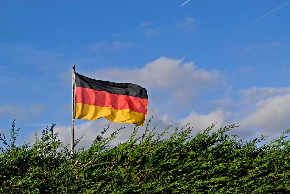 Die schwarz-rot-goldene Dautschlandfahne flattert hinter der Hecke eines Schrebergartens.   |  The german national flag waves behind a hedge of an allotment garden |