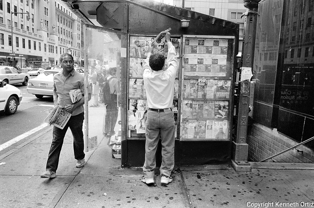 A Newspaper Stand proprietor switches out an old magazine while a young man walks by.