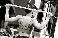 Woman doing pull downs in gym, rear view (B&W)