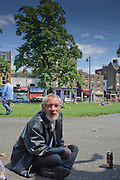 A homeless man sits outside St Mungo's Homeless Hostel on Clapham Common, London.