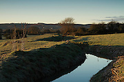 Durleigh Brook as the sun rises over The Meads to the left of frame, with the Quantock Hills in the background, also lit by the dawn light.