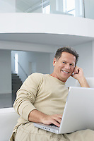 Man with laptop in living room smiling portrait
