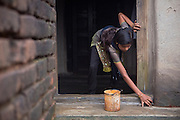 Tabasum Khatun, 14, is washing the entrance of her home in Algunda village, pop. 1000, Giridih District, rural Jharkhand, India.