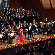 """November 11, 2012 - New York, NY : Accompanied by members of the Metropolitan Opera Orchestra and The New York Choral Society, and conducted by Patrick Summers, soprano Ailyn Pérez (in red) takes a bow -- and blows the audience a kiss -- after performing Jules Massenet's """"Je marche sur tous les chemins!... Obéissons quand leur voix appelle"""" from Manon during the 2012 Richard Tucker Gala and concert in Lincoln Center's Avery Fisher Hall on Sunday evening. """"""""Pérez was this year's recipient of the Richard Tucker award."""""""" CREDIT: Karsten Moran for The New York Times"""