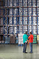 Two Men standing side by side Looking at Full Warehouse Shelves back view