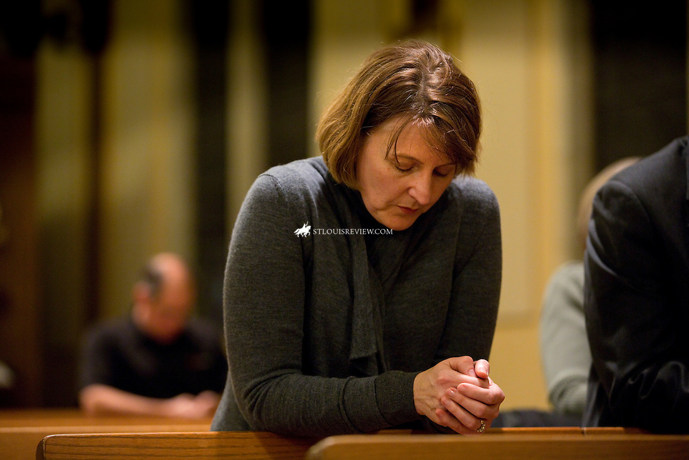 "Lisa Johnston  |  lisajohnston@archstl.org  |  @aeternusphoto  At the start to a night of violence after the announcment of no indictment by the St. Louis County prosecutor's office, people were already praying the rosary at Blessed Teresa of Calcutta Parish in Ferguson.  Archbishop Robert J. Carlson led the prayer service with Father Robert ""Rosy"" Rosebrough, pastor of Blessed Teresa. Catherine Hayek, a member of the parish, prayed the rosary."