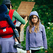 Jade Goodrich puts on a pair of reading glasses taken from the trail sign-in box before hiking Sauk Mountain in the Cascades of Washington State.