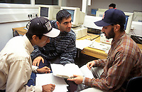 University students discussing a computer project together.