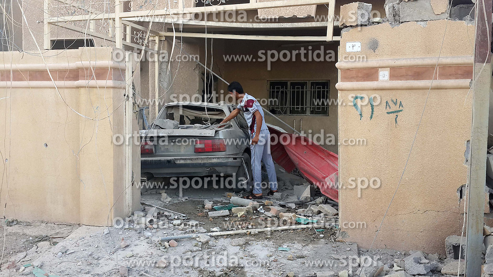 A boy inspects a damaged car after the Iraqi Air Force bombardment in Islamic State (IS) militants-seized city of Fallujah, west of Baghdad, Iraq, on June 11, 2015. At least four citizens were killed and seven wounded during the bombing on Thursday. EXPA Pictures &copy; 2015, PhotoCredit: EXPA/ Photoshot/ Dawood<br /> <br /> *****ATTENTION - for AUT, SLO, CRO, SRB, BIH, MAZ only*****
