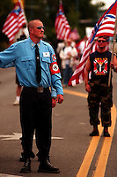 COEUR D ALENE, ID - JULY 17:  An Aryan Nation's security guard walks along Sherman Avenue route during World Congress Parade held in Coeur d'Alene, Idaho, on Saturday, July 17, 2004. About 40 supporters and members marched in downtown Coeur d'Alene for the Aryan World Congress.