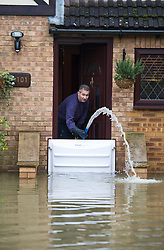 © London News Pictures. 11/02/2014. Wraysbury, UK.  A residents pumping flood water from his home in Wraysbury, Berkshire. The area has been hit hard by recent flooding from the nearby Thames River. Photo credit : Ben Cawthra/LNP