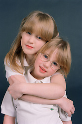 Portrait of young sisters hugging,