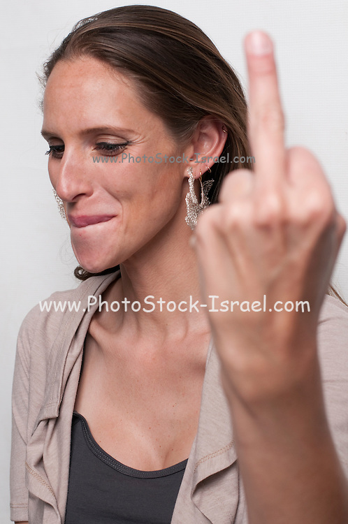 A hip and trendy young woman makes an obscene hand gesture by raising the middle finger Model release available