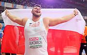 Mar 5, 2017; Belgrade, Serbia; Konrad Bukowiecki (POL) celebrates with Polish flag after winning the shot put in a national record  72-1 (21.97m) during the 34th European Indoor Championships at Kombank Arena. (Jiro Mochizuki/Image of Sport)