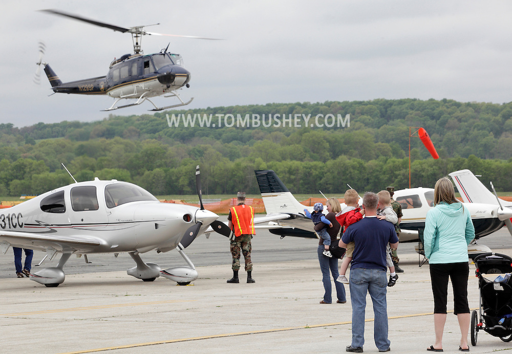 Montgomery, New York - People watch a New York State Police Bell UH-1H Huey II helicopter take off during the Touch-A-Truck event to benefit the United Ways of Orange and Dutchess counties at Orange County Airport on May 14, 2011.