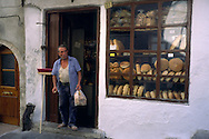 Workman leaving bakers shop carrying bag of bread, Rethymnon Crete Greece....travel, lifestyle