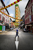 A woman crosses the street in Chinatown, Singapore.