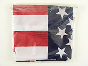 a folded American flag with a Made in China note on the plastic wrapper