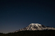 Stars fill the twilight sky over Mount Rainier in this view from near Paradise in Mount Rainier National Park, Washington. The seven stars that make up the Big Dipper are visible just to the left of the volcano's summit. Mount Rainier, which has a summit of 14,411 feet (4,392 meters), is the highest mountain in Washington state and largest volcano in the Cascade Range.