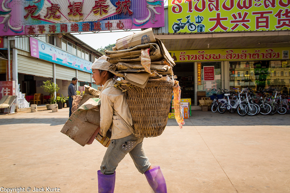13 MARCH 2013 - ALONG HIGHWAY 13, LAOS: A Lao hilltribe girl picks up cardboard for recycling in the Chinese market near the end of Highway 13 in the Boten Special Economic Zone. The SEZ is in Laos immediately south of the Lao Chinese border. It has turned into a Chinese enclave but many of the businesses struggle because their goods are too expensive for local Lao to purchase. Some of the hotels and casinos in the area have been forced to close by the Chinese government after reports of rigged games. The paving of Highway 13 from Vientiane to near the Chinese border has changed the way of life in rural Laos. Villagers near Luang Prabang used to have to take unreliable boats that took three hours round trip to get from the homes to the tourist center of Luang Prabang, now they take a 40 minute round trip bus ride. North of Luang Prabang, paving the highway has been an opportunity for China to use Laos as a transshipping point. Chinese merchandise now goes through Laos to Thailand where it's put on Thai trains and taken to the deep water port east of Bangkok. The Chinese have also expanded their economic empire into Laos. Chinese hotels and businesses are common in northern Laos and in some cities, like Oudomxay, are now up to 40% percent. As the roads are paved, more people move away from their traditional homes in the mountains of Laos and crowd the side of the road living off tourists' and truck drivers.    PHOTO BY JACK KURTZ
