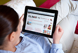 Woman using iPad tablet computer to read Spanish newspaper El Pais online