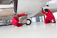 Aviation mechanics inspecting airplane wing