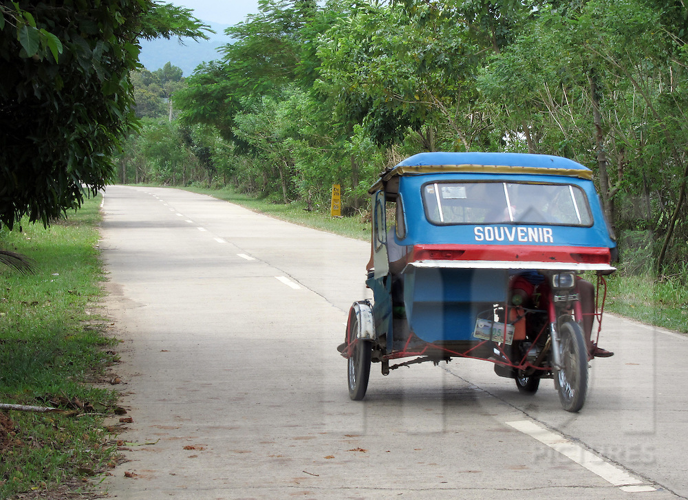Tricycle traveling along quiet road, El Nido, Palawan, Philippines, Southeast Asia