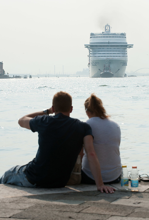 VENICE, ITALY - JUNE 02:  A couple awaits the passage of  MSC Divina along the Zattere  after just few hours stop on June 2, 2012 in Venice, Italy. At 139, 000 tons, the MSC Divina can carry nearly 4,000 passengers. FAI (Fonto Ambientale Italiano) is now supporting Venetians and environmentalists in their protetst against cruise ships sailing in St Mark's basin, arguing that the increased boat traffic on Venice's waterways increases pollution and damages property.  (Photo by Marco Secchi/Getty Images)